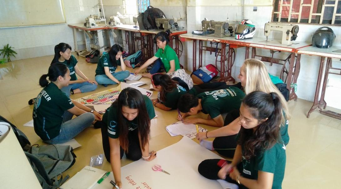 Interns from Projects Abroad can be seen in a classroom making posters to promote nutrition information during their public health internship in Cambodia.